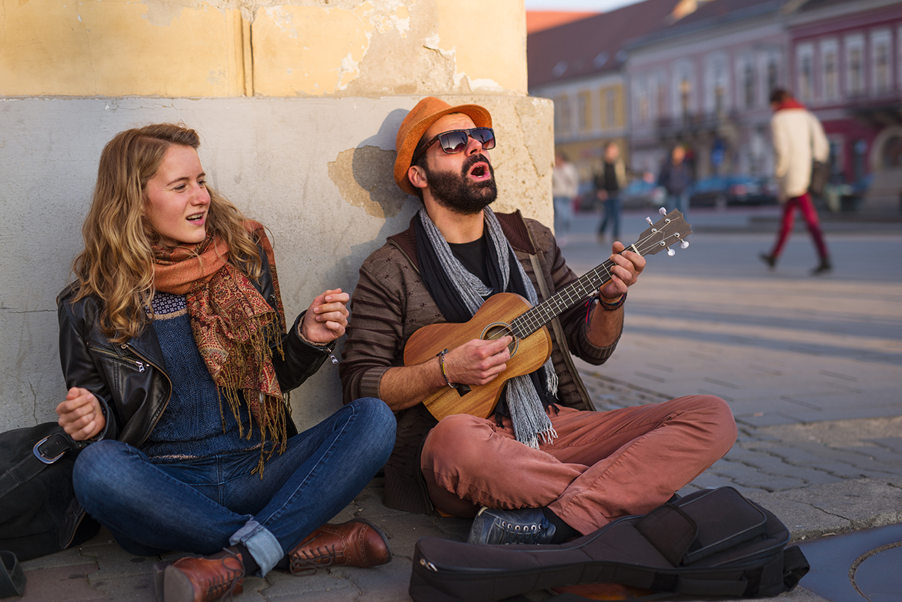 Young people playing music and singing together on the street
